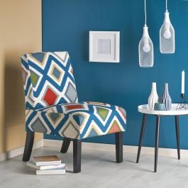 Wielobarwny fotel wypoczynkowy w kąciku salonowym z białym obrazem na tle granatowej ściany i wiszącymi lampami