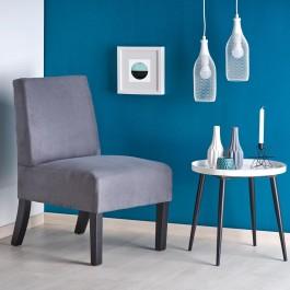 Tapicerowany fotel u boku białego stolika pomocniczego na tle niebieskiej i białej ściany w nowoczesnym salonie