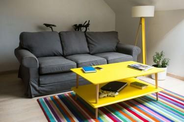 Skandynawski stolik z półką na drewnianych nogach na tle pasiastego dywanu