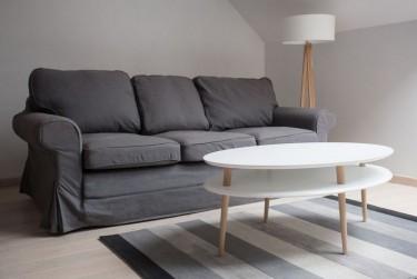Owalny stolik z półką na drewnianych nogach w stylu skandynawskim jako uzupełnienie szarej sofy salonowej