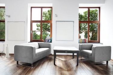 Tapicerowany fotel oraz dwuosobowa sofa w kolorze szarym na metalowych płozach