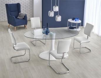 Stół ze szklanym blatem i krzesła na metalowych płozach w jadalni z granatową ścianą oraz fotelem