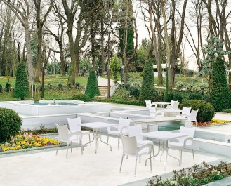 Białe krzesła z profilowanym siedziskiem oraz podłokietnikami i stoły z kwadratowym blatem na aluminiowej podstawie