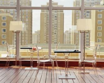 Transparentne krzesła bez podłokietników i stoły z kwadratowym blatem na jednej nodze