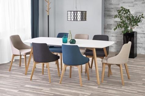 Zestaw z tapicerowanymi krzesłami i lakierowanym stołem do jadalni z szarymi ścianami i czarną donicą