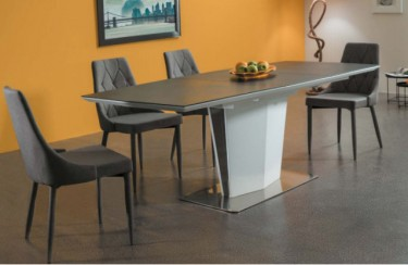 Rozkładany stół ze szklanym prostokątnym blatem i szare pikowane krzesła bez podłokietników