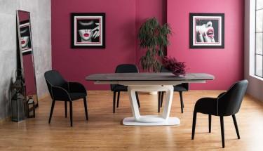 Rozkładany stół z ceramicznym blatem na jednej nodze oraz tapicerowane krzesła z ozdobną lamówką