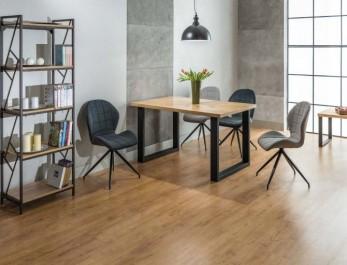 Nierozkładany stół z drewnianym blatem na metalowej podstawie i szare tapicerowane krzesła