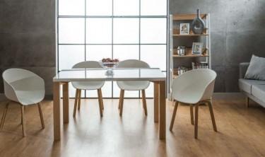 Białe krzesła na drewnianych nogach i stół z prostokątnym blatem o połyskującej powierzchni