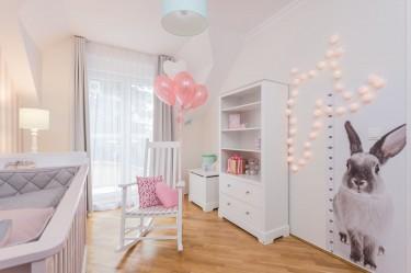 Dziewczęcy pokój z różowymi dodatkami wyposażony w bujany fotel do karmienia oraz skrzynię na zabawki
