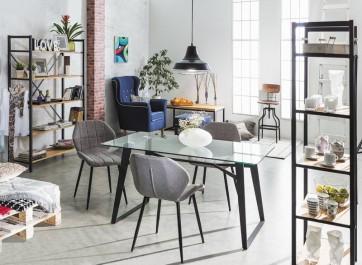 Pojemne regały półkowe w stylu industrialnym oraz stół ze szklanym blatem i tapicerowane krzesła