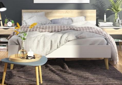Łóżko na drewnianych nóżkach w stylu skandynawskim w nowoczesnej sypialni na tle szarych ścian