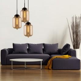 Wisząca lampa z trzema kloszami i ozdobnymi żarówkami oraz wygodna sofa salonowa