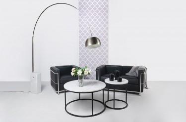 Metalowa lampa łukowa na marmurowej podstawie i czarna skórzana sofa z fotelem