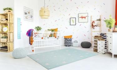 Miętowy dywan w białe groszki i gwiazdki oraz łóżeczko ze szczebelkami w kolorze białym
