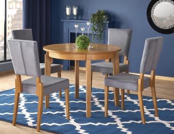 Okrągły stół do jadalni oraz tapicerowane krzesła z wysokim oparciem