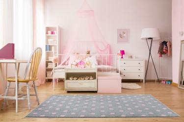 Szary dywan w różowe groszki oraz łóżko uzupełnione bajkowym baldachimem