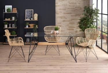 Stół ze szklanym blatem na designerskiej podstawie oraz rattanowe krzesła