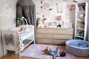 Dekoracyjna lampa na drewnianej podstawie oraz różowy dywan w chmurki
