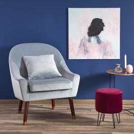 Kącik wypoczynkowy w salonie z tapicerowanym fotelem i pufą na metalowych nóżkach