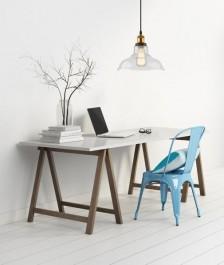 Drewniane biurko i niebieskie krzesło z metalu oraz wisząca lampa w stylu industrialnym