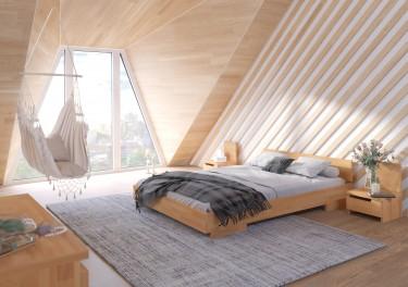 Sypialnia na poddaszu z dużym drewnianym łóżkiem i szafkami nocnymi