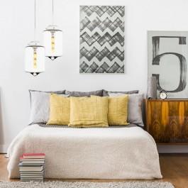 Wysokie łóżko z miękkimi poduszkami oraz szklane lampy wiszące z transparentnymi kloszami