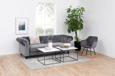 Nowoczesna kanapa i fotel bujany tapicerowane tkaniną welwetową w salonie z drewnianą podłogą