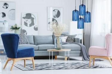 Nowoczesna lampa wisząca z czterema kloszami i tapicerowane fotele na drewnianych nóżkach