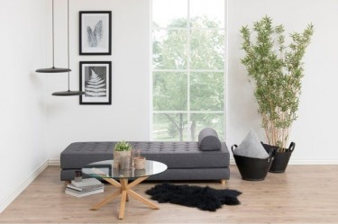 Rozkładana kanapa w kolorze szarym w salonie ze szklanym stołem