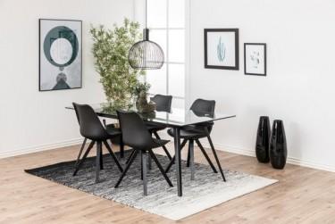 Szklany stół na 4 nogach z metalu z czarnymi krzesłami w otwartej jadalni z wysokim oknem