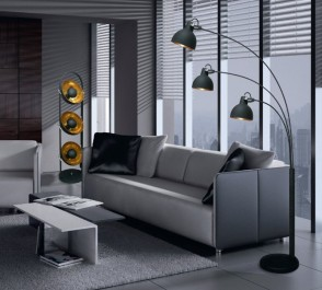 Designerskie lampy podłogowe w kolorze czarnym i komfortowa sofa z miękkimi poduchami