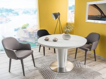 Okrągły stół z funkcją rozkładania na jednej nodze w zestawieniu z tapicerowanymi krzesłami w niewielkiej jadalni