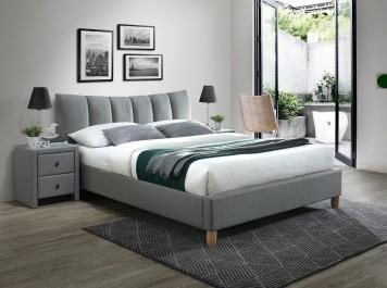 Tapicerowane łóżko na drewnianych nogach z wysokim zagłówkiem i szafka nocna z szufladami