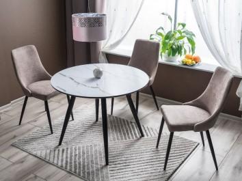 Okrągły stół na metalowych nogach z tapicerowanymi krzesłami na popielatym dywanie